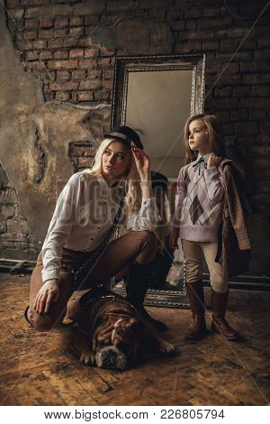 Child Girl With Woman In Image Of Sherlock Holmes Stands Next To English Bulldog On Background Of Ol
