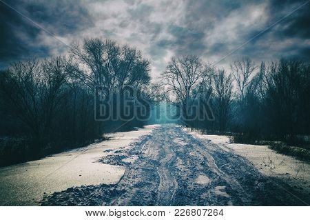 Winter Road In Light Fog In The Mystical Forest. The Sky In Dark Clouds.