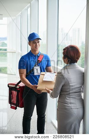 Smiling Young Delivery Man Giving Package With Lunch To Busines Lady