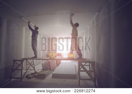 Workers Are Installing Ceiling From Wooden Platform In Apartment Is Under Construction, Remodeling,