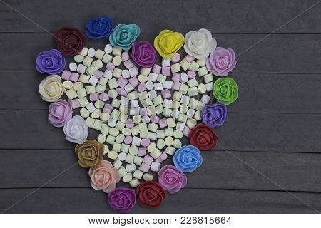Sweet Marshmallows In Heart Shape Decorated With Flowers On Wood Background. Valentine Day Concept