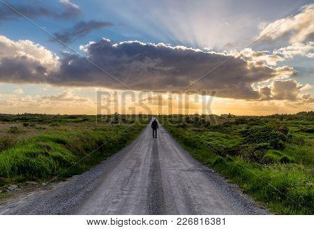 Man Walking On An Abandoned Road In Beautiful Sunset Landscape