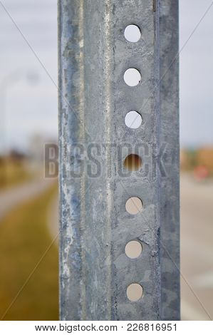 A Closeup Of A Galvanized Road Sign Post Appears Against The Road As A Background.
