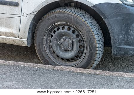 A Worn Winter Car Tire At A Parked Car