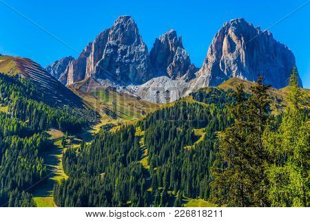 The coniferous forests at the foot of limestone and dolomite rocks. The most picturesque route in the Italian Dolomites, the Southern Limestone Alps. The concept of active and car tourism