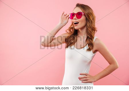 Sexual magnificent woman with brown hair in swimsuit and sunglasses smiling and looking aside, isolated over pink background