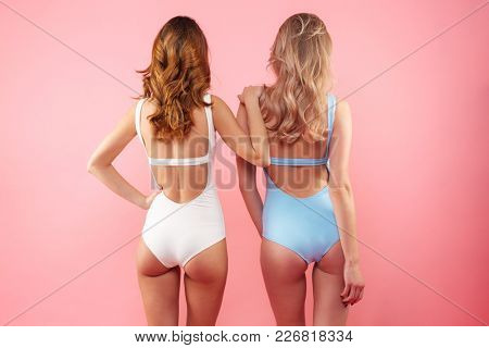 Portrait of two sexual young girls 20s wearing colorful one-piece swimsuits standing backward on camera isolated over pink background