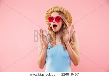 Blonde young girl in sunglasses wearing colorful one-piece swimsuit and straw hat admiring while looking aside, isolated over pink background