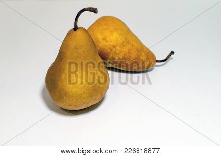 Two Pears On White Surface, One Standing Up Tall And The Other One Laying Down.