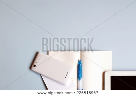 Office Desk Table Notebook, Smart Phone, Tablet And Pen. Top View With Copy Space. Working Desk Or S
