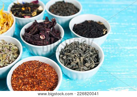 Herbs And Teas In Bowls To Make Tea On Blue Table Background Cl