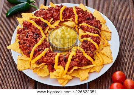 National Mexican And Chilean Dish On A Wooden Table. Homemade Potato Chips With Tomato Sauce, Beans