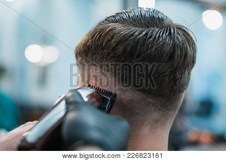 Getting Perfect Shape. Close-up Side View Of Young Bearded Man Getting Beard Haircut By Hairdresser