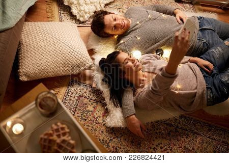 leisure, hygge and people concept - happy couple with garland lying on floor at home and making selfie by smartphone
