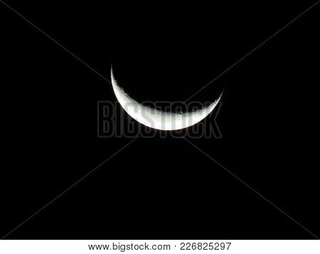 Crescent Waning Moon With Craters And Earth Shine