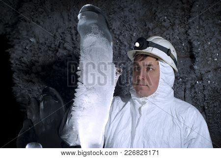Speleologist In A Cave Examines A Giant Ice Stalagmite Covered With Hoarfrost, Against A Background