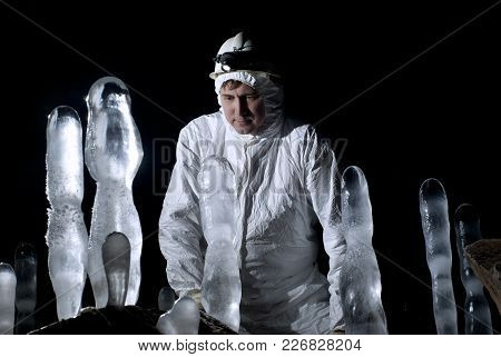 Speleologist In A Cave Looks At The Ice Structures, Against A Dark Background