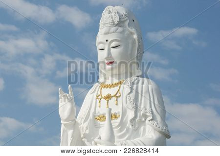 Guan Yin Statue With Clear Blue Sky And Water Bottle In Hand