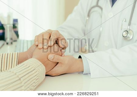 Friendly Man Doctor Hands Holding Patient Hand Sitting At The Desk For Encouragement, Empathy, Cheer