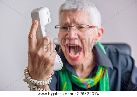 Angry, Enraged Senior Woman Yelling At A Landline Office Phone, Unhappy With Customer Service Provid