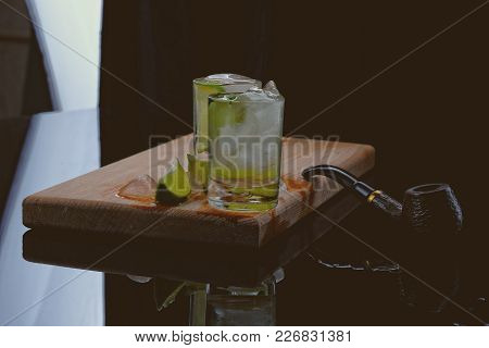 Two Shots Of Strong Alcohol On Board Of Wood, In Which The Ice Cubes And Lime, Cut Into Wedges. Lyin