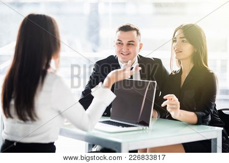 Young Love Couple Sitting At A Desk In The Office Of Their Agent Or Adviser Discussing An Investment