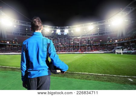 Boy with a ball stands in front of an empty football stadium at night, collage