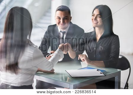 Happy Young Couple Meeting With A Broker In Her Office Leaning Over The Desk To Shake Hands, View Fr