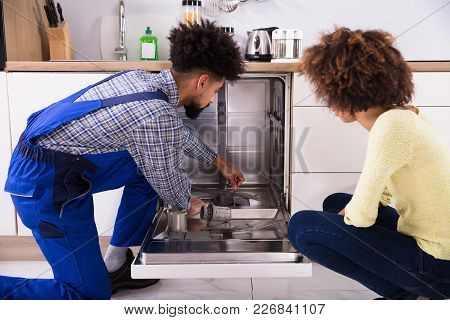 Young Woman Looking At Male Repairman Fixing Dishwasher In Kitchen