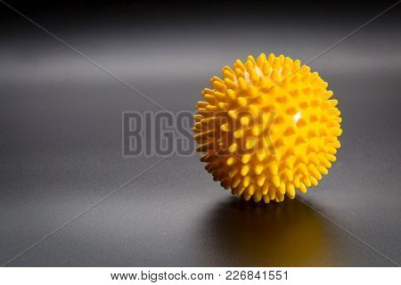 spiky rubber  ball roller for self massage, reflexology and myofascial release, black background with a shadow