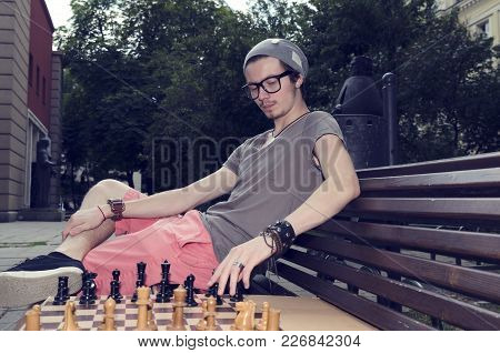 Young Man Playing Chess In The Park