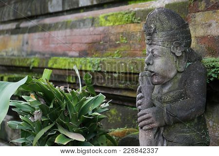 Statue In Bali Indonesia With Moss And Wall
