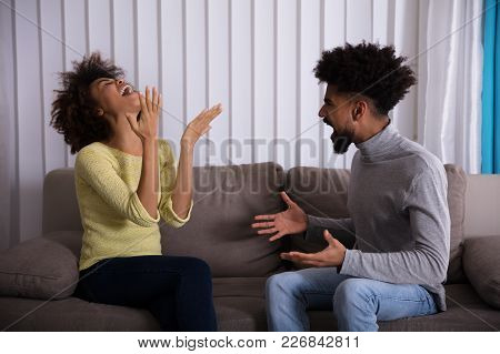 Young Couple Sitting On Sofa Quarreling With Each Other At Home