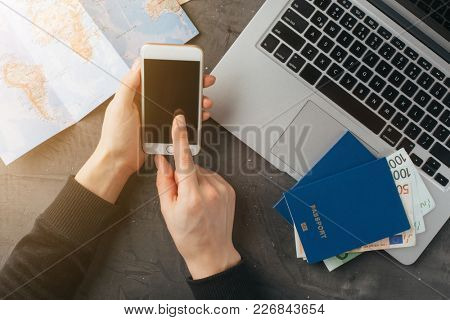 Female hands hold a smartphone over a laptop. Concept of buying online, planning a trip. Top view