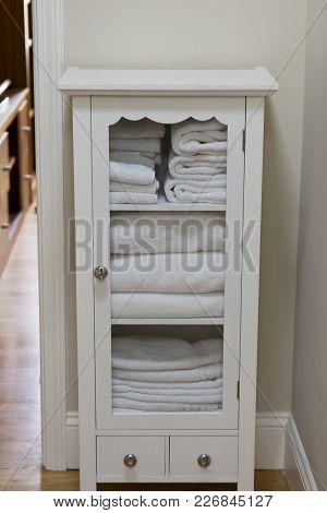 White Linen Cabinet With Folded White Towels And Sheets.