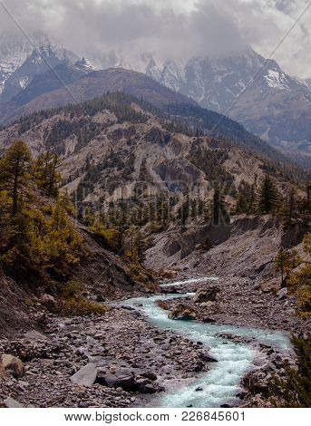 Scenic Landscape With Blue River, Pine Forest, Cloudy Peaks And Snow Mountain Background. Annapurna