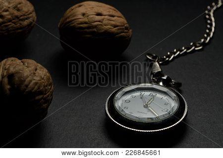 Pocket Watch On Dark Table With Walnuts