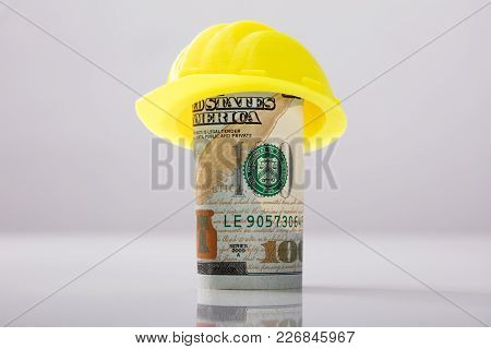 Close-up Of Yellow Hard Hat Over Rolled Up American Banknote On White Background
