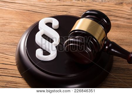 Elevated View Of Gavel And Paragraph Sign On Wooden Desk