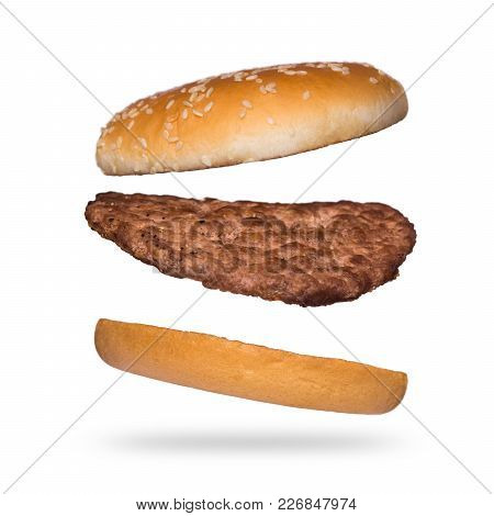 Flying Burger Isolated On White Background. Ingredients For Burger. Bun With Sesame And Beef Cutlets