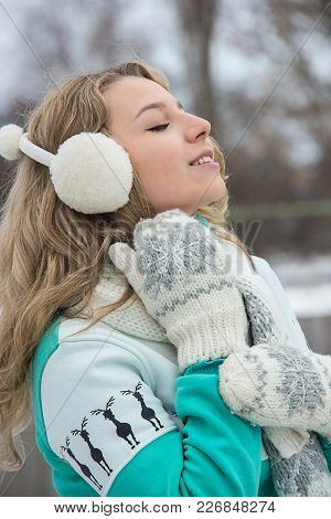 Girl In Mittens And Headphones In A Green Sweater On The Street, On The Ice Arena