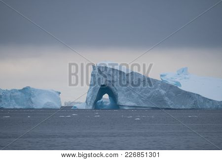 A Large Iceberg With An Archway Floating In Charlotte Bay In Antarctica. Dense Clouds Are Overhead A
