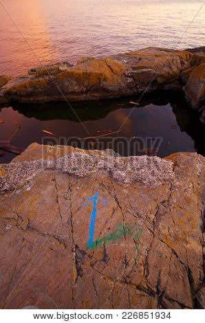 Warm Light Of Sunset Illuminates A Tide Pool And A Blue Painted Arrow On The Rocks Near Victoria, Br