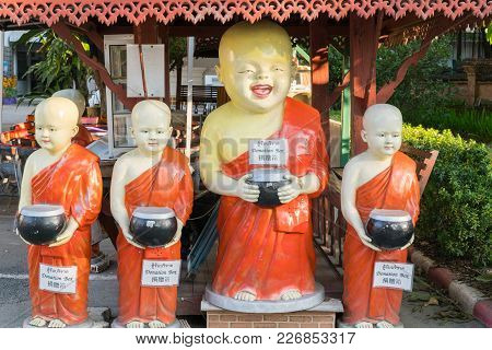 Chaing Mai Thailand - January 29 2018; Statues Of Four Smiling Buddhist Novice Monks Holding Alms Co