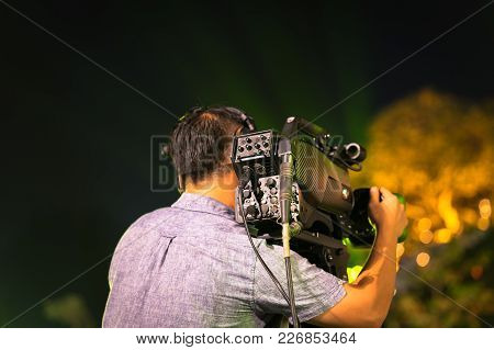 Back View Of Professional Television Camera In Event At Night.