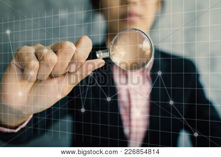 Business Women Holding Magnifying Glass With Financial Graph