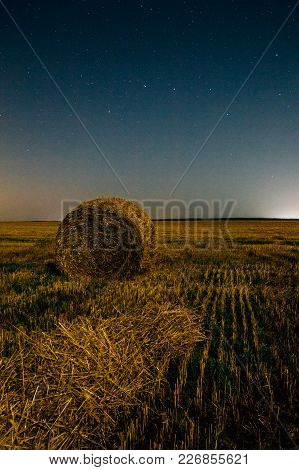 Night Field With A Stack Of Dry Hay Under A Starry Night Sky. Constellation Of The Ursa Major Bear O