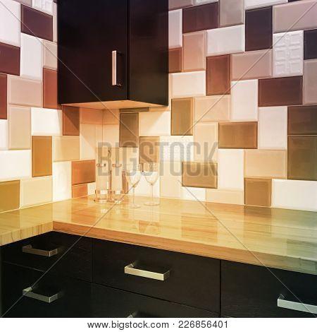 Modern Kitchen Cabinets And Tiled Backsplash In Warm Colors.
