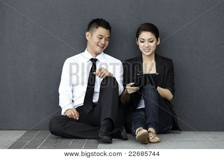Asian Business Couple Using An Ipad