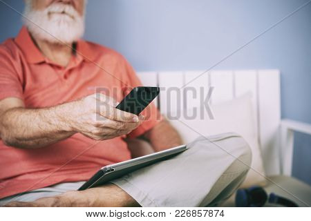 Senior Man Holding Remote Control In His Hand To Switch Channels, Digital Tablet On His Lap